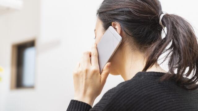 電話で手続きする女性